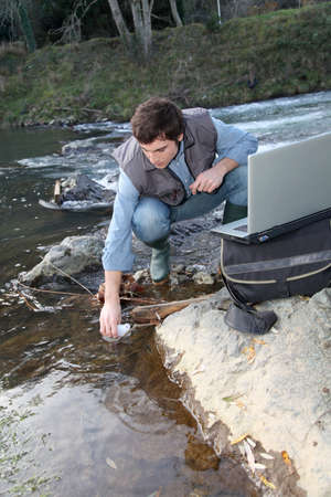 water quality: Man scientist testing quality of water in river