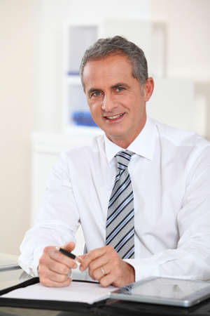 mature men: Portrait of businessman sitting at his desk Stock Photo