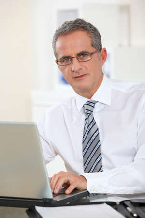 Portrait of businessman working on laptop computer photo