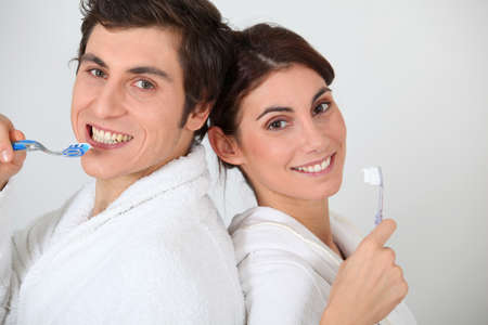 Portrait of couple brushing their teeth photo