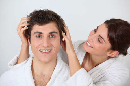 Young woman putting her hands in her boyfriends hair photo