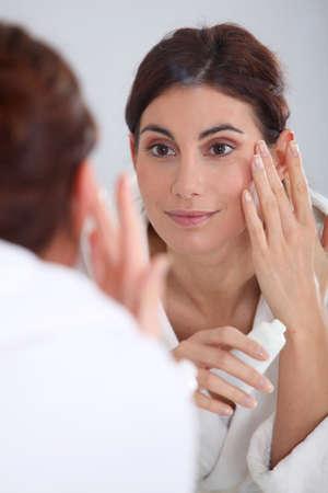 Portrait of beautiful woman applying moisturizer  photo
