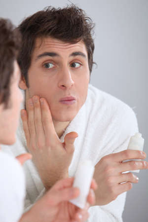 Portrait of man applying moisturizer on his face photo