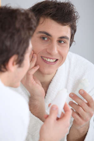 Portrait of man applying moisturizer on his face photo
