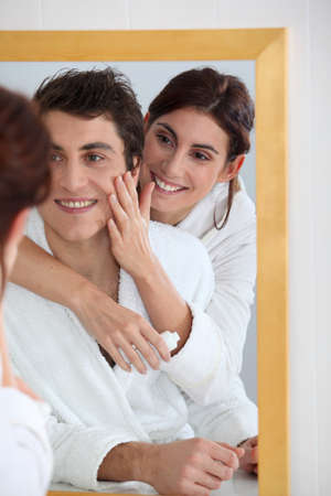 Woman applying moisturizer on boyfriends cheek photo