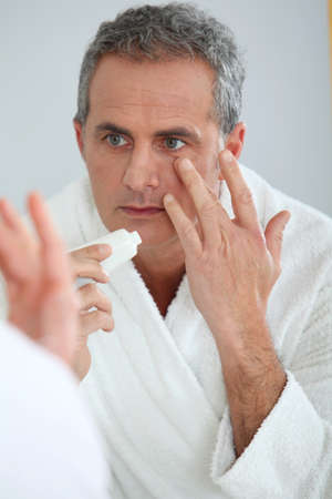 men 45 years: Portrait of mature man applying moisturizer on his face