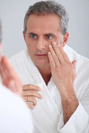 Portrait of mature man applying moisturizer on his face photo