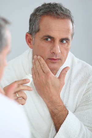 face cream: Portrait of mature man applying moisturizer on his face