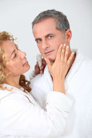 Woman applying moisturizer on boyfriend's cheek Stock Photo - 8741890
