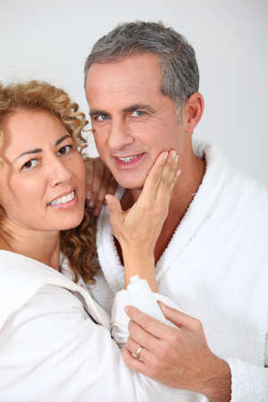 Woman applying moisturizer on boyfriends cheek photo