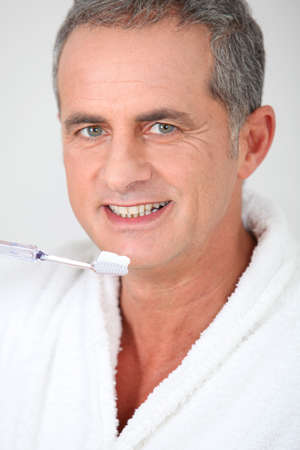 Portrait of man brushing his teeth photo