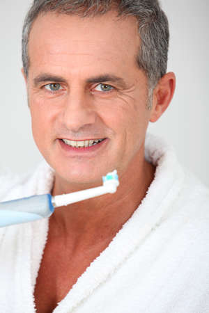 dentalcare: Portrait of mature man using electric toothbrush Stock Photo