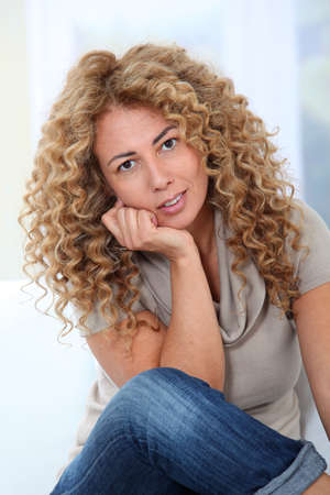 hair curly: Hermosa mujer rubia relajante en sof�