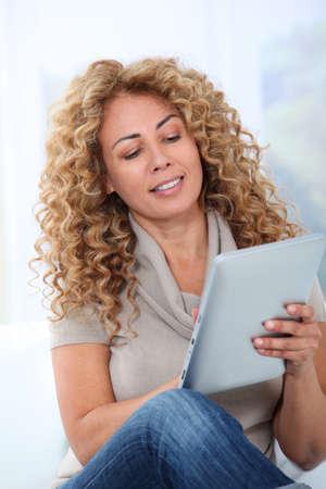 electronic pad: Woman in sofa using electronic pad