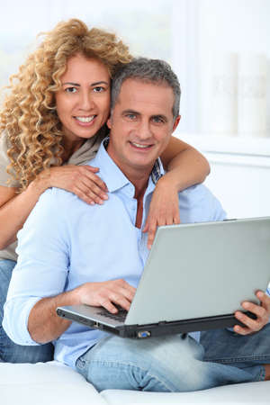 ethnic mix: Couple surfing on internet at home