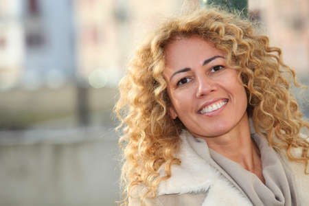 ethnic mix: Portrait of smiling blond woman in town Stock Photo