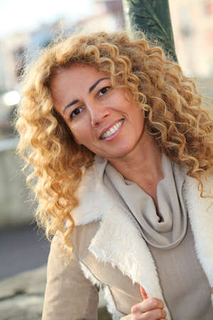 Portrait of smiling blond woman in town photo