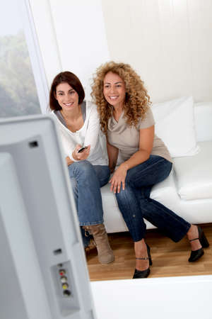Girl friends watching tv at home photo