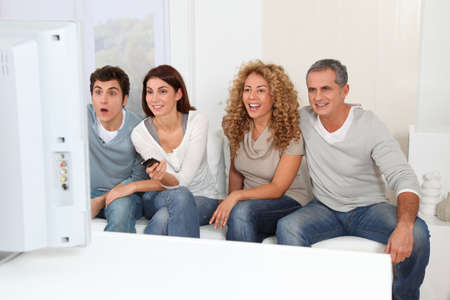 show home: Group of friends sitting in sofa watching sport game on tv Stock Photo
