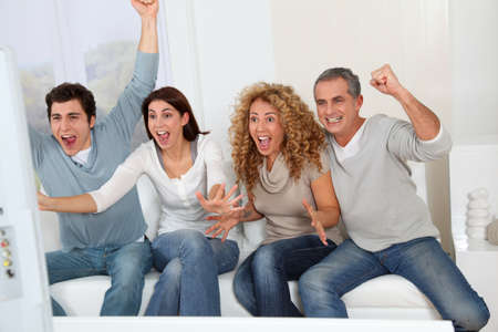game show: Group of friends sitting in sofa watching sport game on tv Stock Photo