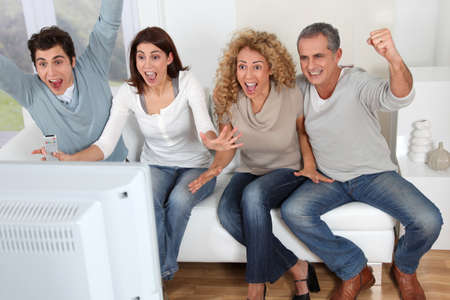 sport fan: Group of friends sitting in sofa watching sport game on tv Stock Photo