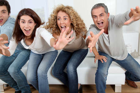 couple watching tv: Group of friends sitting in sofa watching sport game on tv Stock Photo