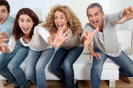 viewing: Gruppo di amici, seduto nel divano a guardare la partita lo sport in tv Archivio Fotografico
