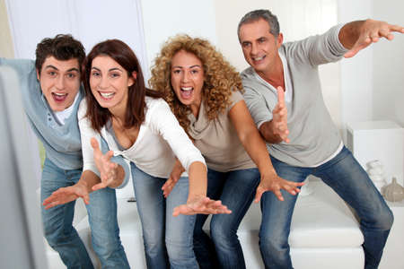 Group of friends sitting in sofa watching sport game on tv Stock Photo - 8741970