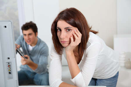 Young woman fed up with boyfriend playing video game photo