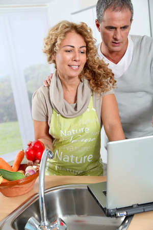 Couple cooking in kitchen with laptop computer photo
