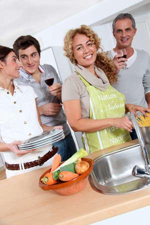 cocineras: Grupo de amigos prepraing cena en casa de cocina Foto de archivo