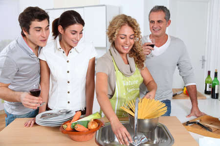 cooker: Group of friends prepraing dinner in home kitchen