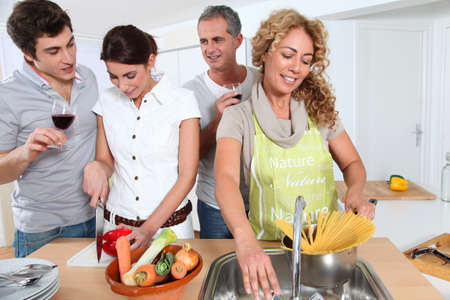 30s adult: Group of friends prepraing dinner in home kitchen
