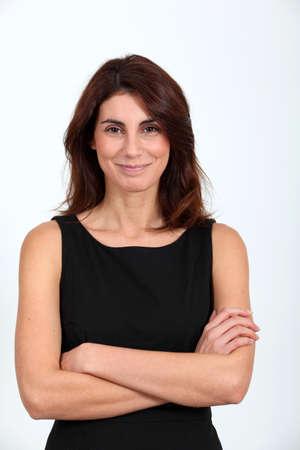 Femme en robe noire avec les bras croisés Banque d'images