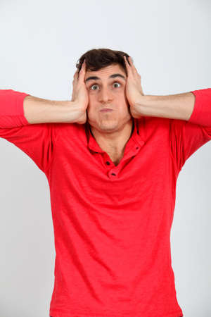 stifle: Man with hands on ear doing weird face Stock Photo