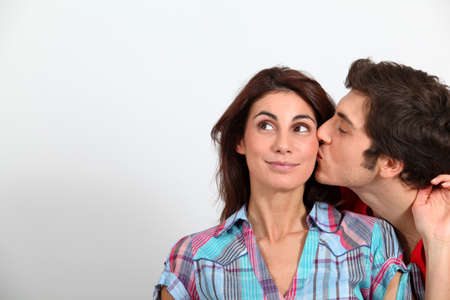 cheeks: Young man kissing girlfriend on cheek Stock Photo
