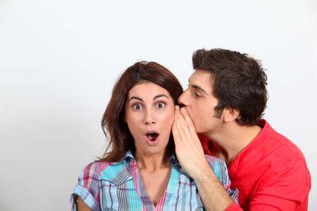 secret love: Young man whispering in his girlfriends ear