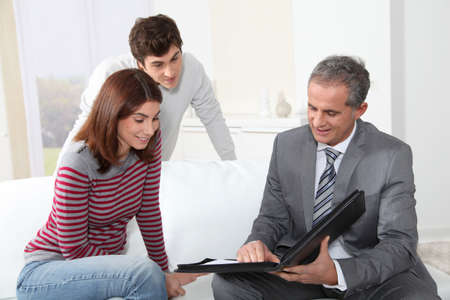 Young couple sigining renting contract with real estate agent Stock Photo - 8741716