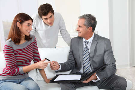 Young couple sigining renting contract with real estate agent photo