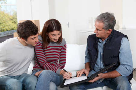 Young couple signing contract for home moving photo