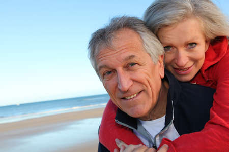Senior man giving piggyback ride to woman by the sea photo
