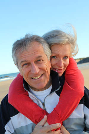 Senior man giving piggyback ride to woman by the sea Stock Photo - 8741847