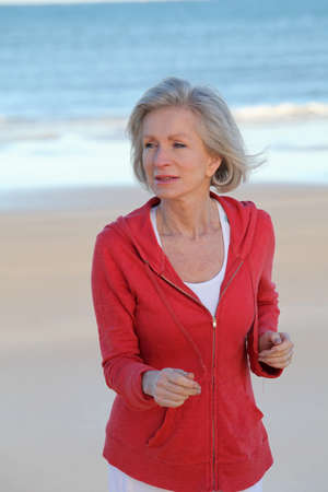 senior woman exercising: Senior woman running by the beach Stock Photo