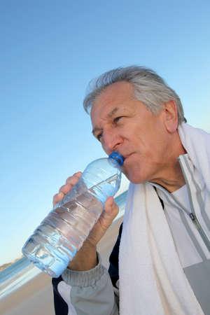 Actieve senior drinkwater uit de fles op het strand