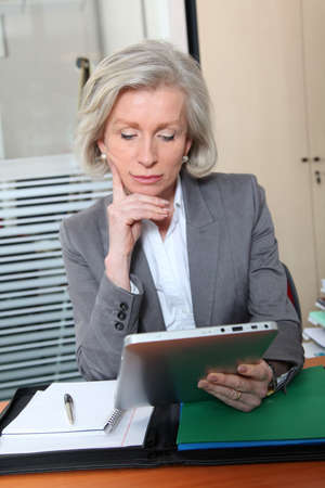 Senior office worker in office with electronic pad photo