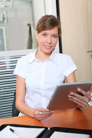electronic pad: Young woman in office iwith electronic pad