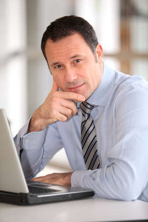 Portrait of businessman in front of laptop computer photo