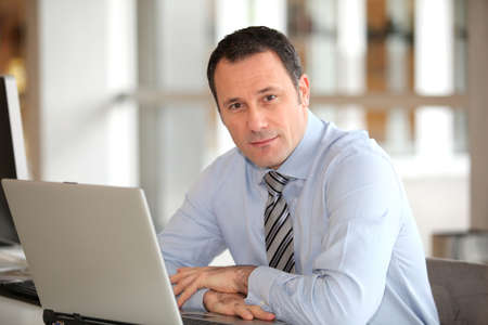 man sit: Portrait of businessman in front of laptop computer Stock Photo