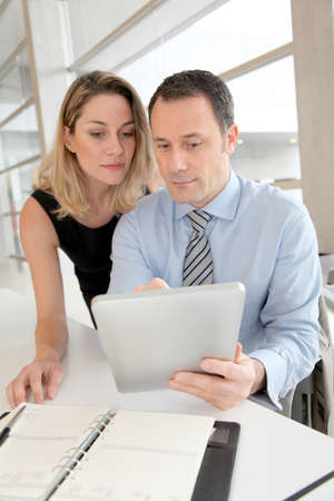 Business people working on electronic tablet photo