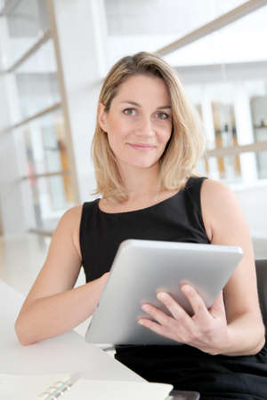 android tablet: Businesswoman in the office working on electronic tab